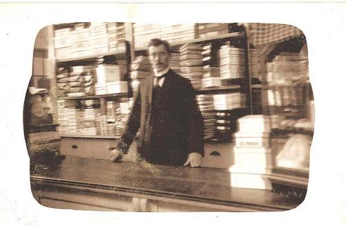 Rients van der Zee achter de toonbank van zijn winkel Oude Delft 103, ergens tussen 1913 en 1919.